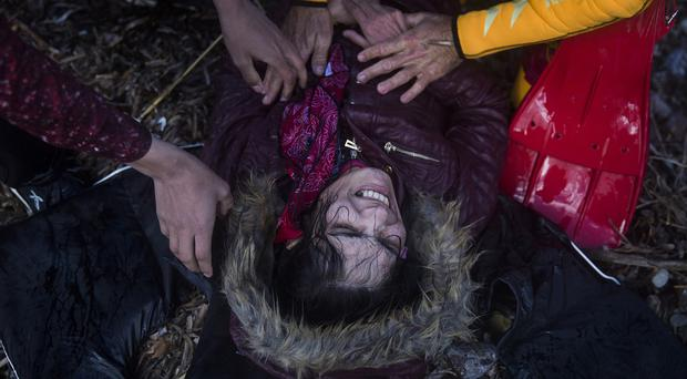 A woman receives treatment after her arrival in bad weather on the Greek island of Lesbos on a dinghy on Wednesday (AP)