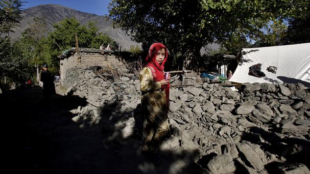 A girl walks in the rubble of destroyed homes after the earthquake in Chitral, Pakistan. (AP)