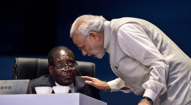 Indian prime minister Narendra Modi speaks with Zimbabwe's president Robert Mugabe during the India Africa Forum Summit in New Delhi (AP)