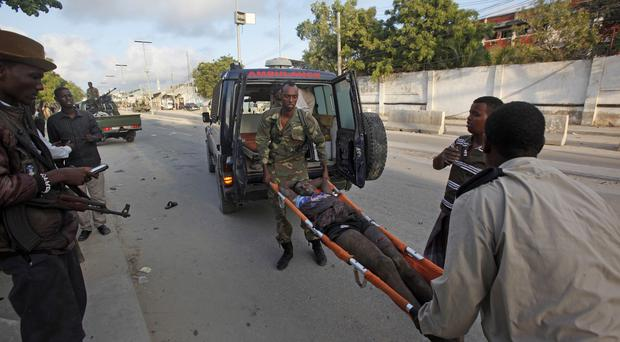 Somali policemen carry a wounded person to an ambulance outside the Sahafi Hotel in Mogadishu (AP)