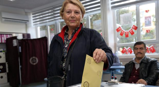 A Turkish woman casts her vote at a polling station at a primary school in Ankara (AP)