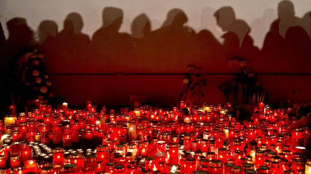 People cast shadows on a wall as they wait to light candles and lay flowers at the scene of the tragedy (AP)