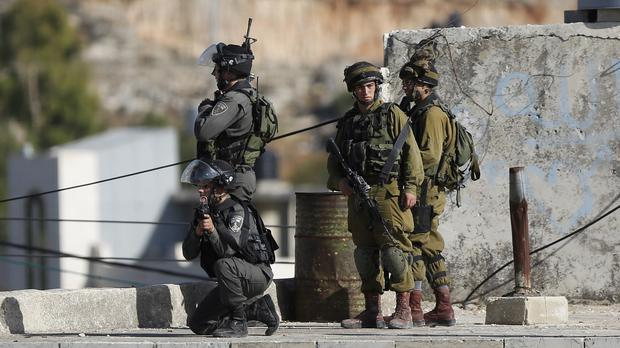 Israeli troops at the scene of a stabbing attempt east of the West Bank city of Hebron (AP)
