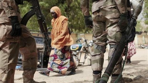 A woman walks past Nigerian soldiers at a checkpoint in Gwoza, Nigeria, a town newly liberated from Boko Haram (AP)