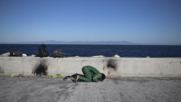 An Iraqi man prays at the port of Mytilene on the island of Lesbos, Greece (AP)