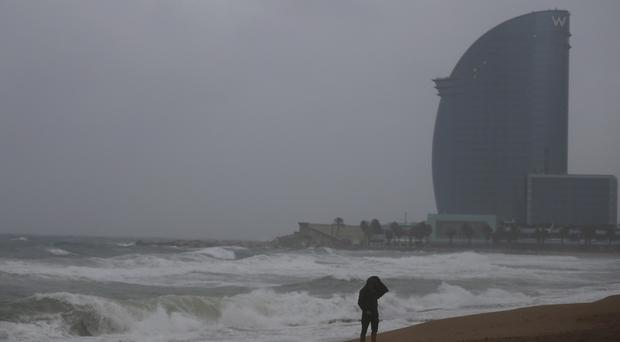 A man walks along the beach in stormy weather in Barcelona, Spain (AP Photo/Manu Fernandez)
