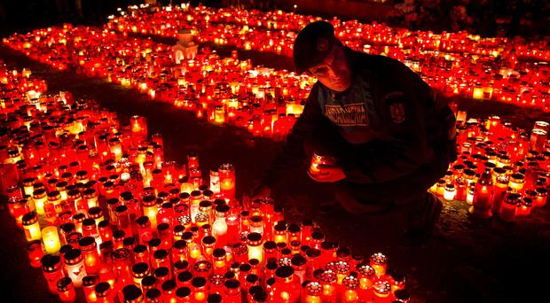 A police officer places a candle, collected from people waiting to pay respects to the victims of a fire in Bucharest (AP)