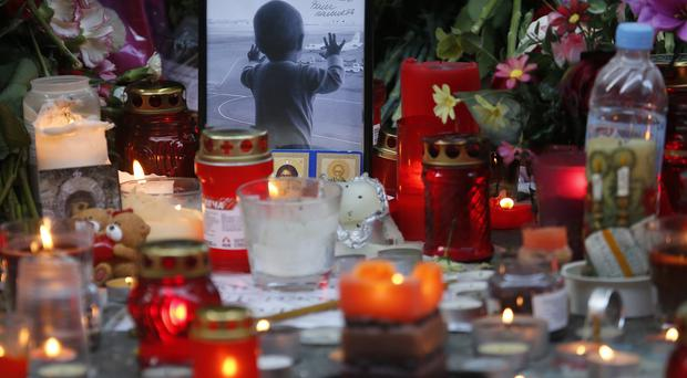 A portrait of 10-month-old Darina Gromova, a victim of the Sinai plane crash, is surrounded by flowers and candles at an entrance to Pulkovo airport near St Petersburg (AP)