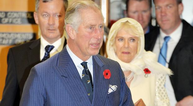 Charles and Camilla take shelter from the wet weather in Wellington Airport's VIP terminal at the start of their week-long tour of New Zealand before travelling on to Australia