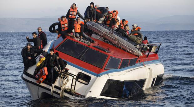 Refugees and migrants perch atop a heavily-listing boat as they try to travel from the Turkish coast to Skala Sykaminias on the north-eastern Greek island of Lesbos (AP)