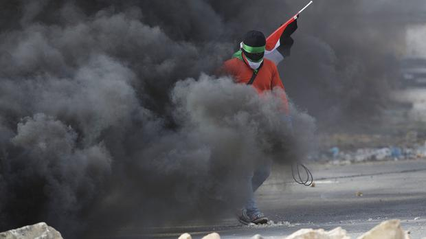 A masked Palestinian holds a national flag during clashes with Israeli troops outside Ofer military prison near the West Bank city of Ramallah (AP)
