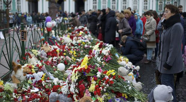 People gathered to lay flowers in memory of the plane crash victims at Dvortsovaya Square in St Petersburg (AP)