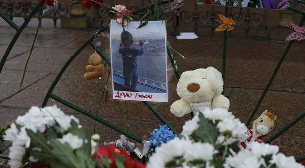 A portrait of 10-month-old Darina Gromova, one of the Metrojet plane crash victims, is surrounded by flowers and toys at Dvortsovaya (Palace) Square in St Petersburg (AP)