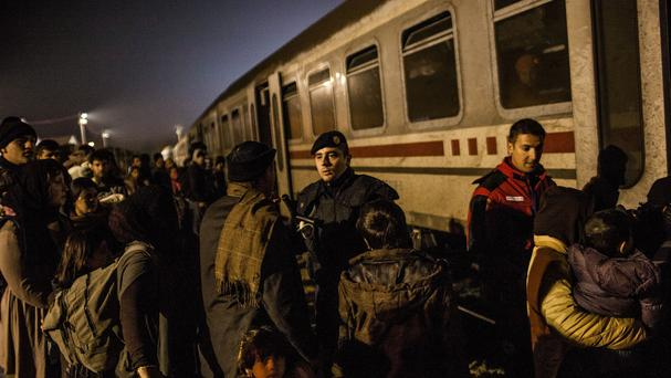 Migrants board a train on the way to Slovenia within a temporary camp in Slavonski Brod, Croatia (AP)