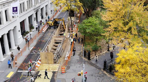 A plywood wall surrounds the opening to an underground construction area (AP)