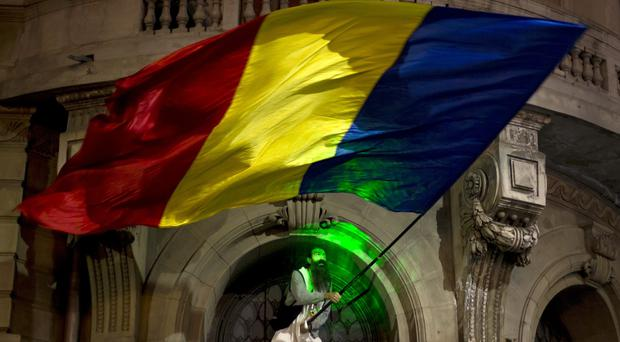 A man waves a large Romanian flag during the third day of protests calling for early elections in Bucharest (AP)