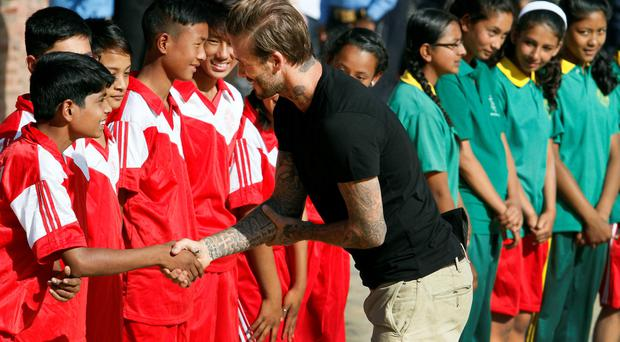 Unicef goodwill ambassador David Beckham enjoys a kickabout in Kathmandu yesterday with excited Nepalese youngsters during a visit for the UN Children's Fund