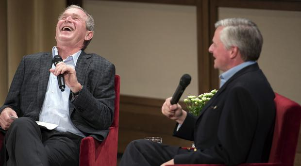 George W Bush, left, reacts to a joke during a conversation with author Jon Meacham about his biography of Mr Bush's father, former president George HW Bush (AP)