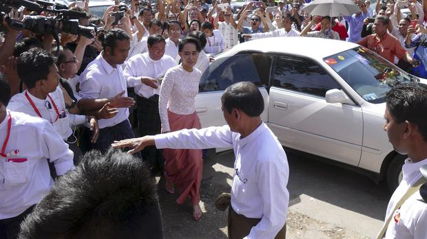 Opposition leader Aung San Suu Kyi is mobbed by supporters as she arrives at the headquarters of her National League for Democracy party in Rangoon (AP)