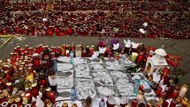 Photographs of the victims are surrounded by candles outside the Colectiv nightclub in Bucharest, Romania (AP)