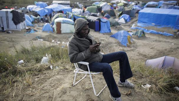 A man uses his smartphone as he sits on a chair inside the migrant camp near Calais, northern France (AP)
