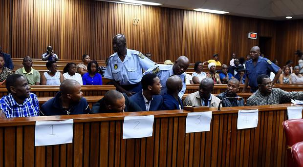 The former policemen appear at the High Court in Pretoria, South Africa (AP)