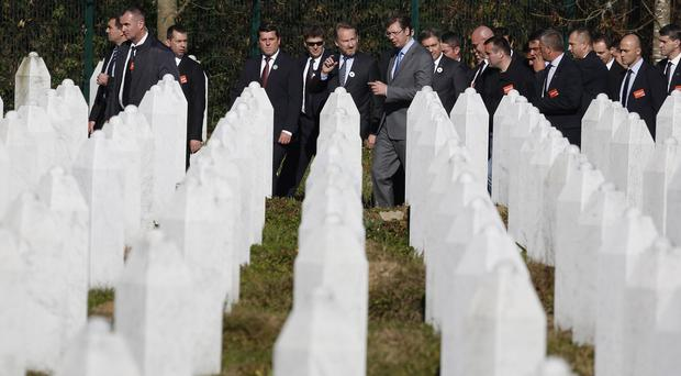 Serbian prime minister Aleksandar Vucic, centre right, walks among grave stones at the memorial centre Potocari, near Srebrenica (AP)