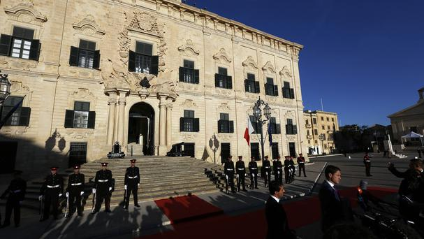 Maltese honour guards stand outside the Auberge de Castille palace as they wait for the arrival of head of states for a summit on migration (AP)