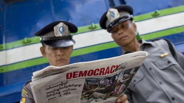 Police officers read a copy of the newspaper Democracy Today in Yangon (AP)