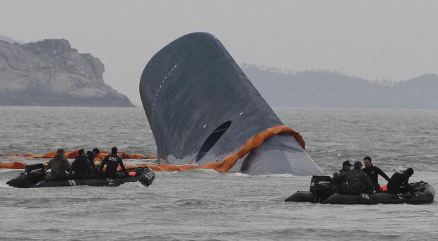South Korean coast guard personnel search for missing passengers after the ferry Sewol sank (AP)