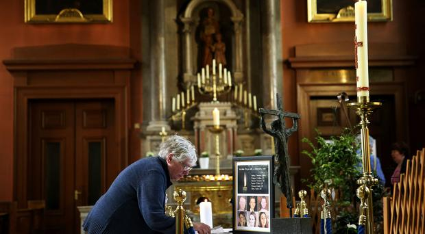 Members of the public sign a book of condolence at the Pro-Cathedral in Dublin for those killed in the Berkeley balcony collapse