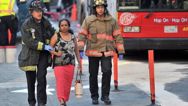 Firemen walk a woman towards an ambulance near Union Square in San Francisco after the tour bus crash (AP)