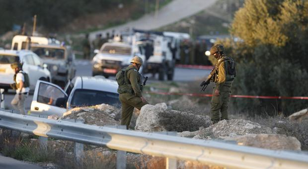 Israeli soldiers stand at the scene of a shooting attack near the West Bank city of Hebron (AP)