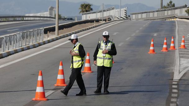 Turkish police officers guard the main road leading to the resort area outside Antalya where the G20 summit is scheduled to take place (AP)