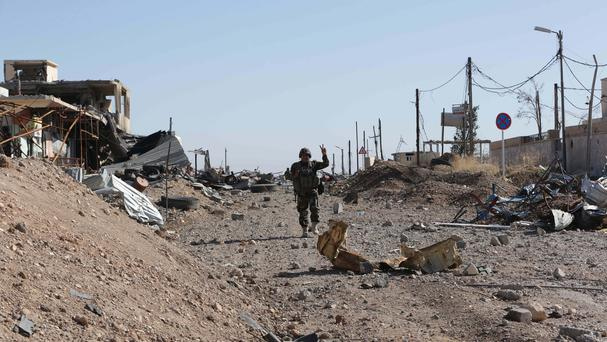 A Kurdish Peshmerga fighter walks through the town of Sinjar after it was retaken from Islamic State (AP)