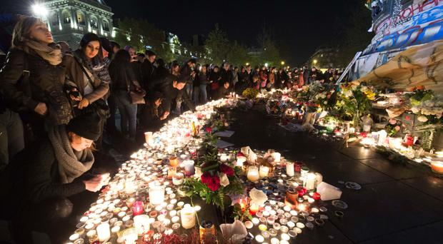 People gather at a memorial to the victims at the place de la Republique in Paris