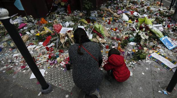 A woman and child kneel in front of the Carillon restaurant one of the targets of Friday's attacks in Paris (AP)
