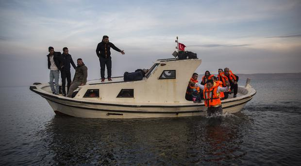 Migrants disembark from a small boat as they arrive from the Turkish coast on the north-eastern Greek island of Lesbos (AP)