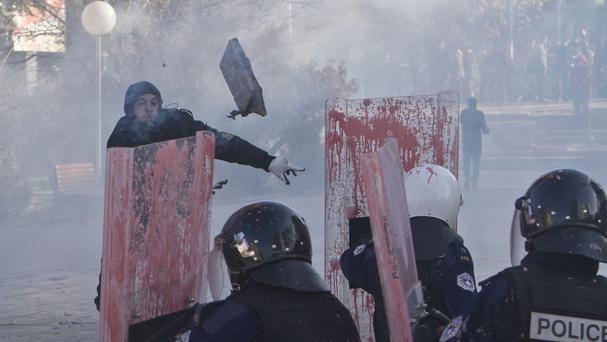 A supporter of the opposition parties in Kosovo throws a rock towards police in riot gear in Pristina (AP)