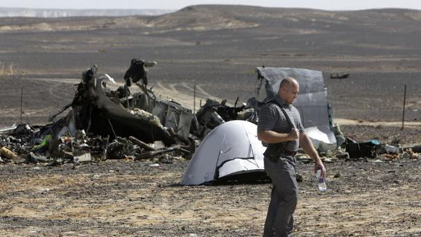 A Russian investigator walks near wreckage a day after a passenger jet bound for St Petersburg crashed in Egypt (AP)