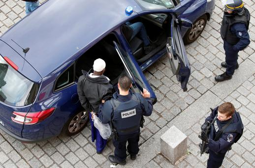Police officers arrest a man following yesterday's raids