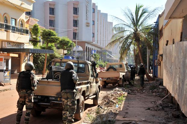 Malian troops take position outside the Radisson Blu in Bamako after gunmen went on a shooting rampage at the luxury hotel in Mali's capital
