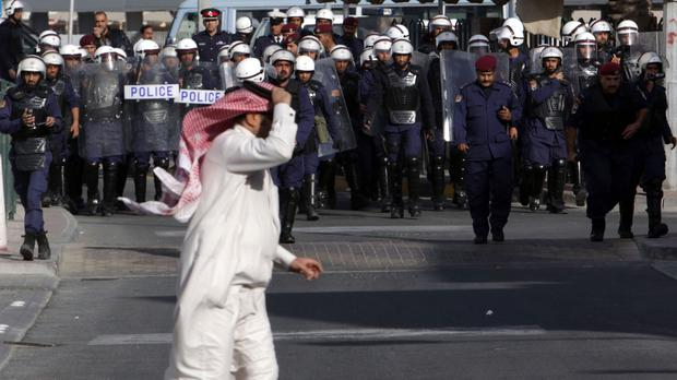 Hassan al-Marzooq, deputy general secretary of the opposition National Democratic Assemblage society, runs across a street in Manama in 2012 as riot police move in (AP)