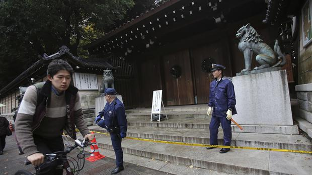 Police officers stand guard outside the south gate of Yasukuni shrine in Tokyo (AP)