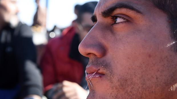 A migrant sits with his mouth sewn shut during a protest near the village of Idomeni. (AP)