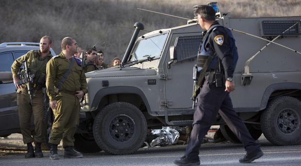Israeli soldiers at the scene of a stabbing attack near of the West Bank city of Nablus (AP)