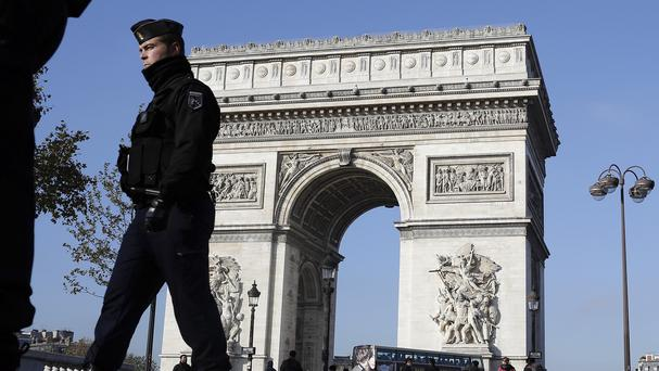 A French gendarme officer patrols in front of the Arc de Triomphe, on the Champs Elysees in Paris (AP)
