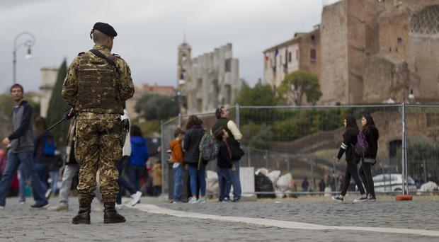 An Italian soldier patrols near Rome's Colosseum, as the US State Department issues a travel warning for its citizens (AP)