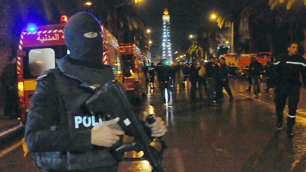 A hooded police officer at the scene of the bus explosion in the centre of Tunis (AP)