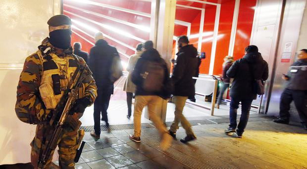 A police officer guards the entrance to a subway station in Brussels (AP)